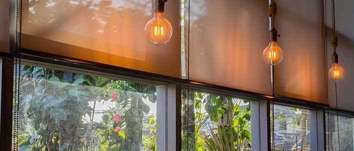 Commercial roller blinds behind dangling dim lit lightbulbs