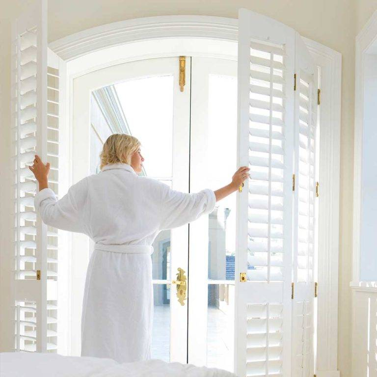 woman opening plantation shutters in the morning